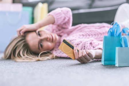 selective focus of credit card in hand of woman lying on floor at home