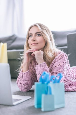 selective focus of dreamy woman holding dollar banknotes while lying near laptop