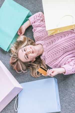top view of cheerful woman holding credit card and lying on floor near shopping bags