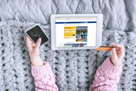 cropped view of woman holding credit card and smartphone near digital tablet with booking app on screen