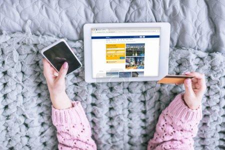 Foto de Recorta la vista de la mujer que sostiene la tarjeta de crédito y teléfono inteligente junto a la tableta digital con reserva de la aplicación en pantalla - Imagen libre de derechos