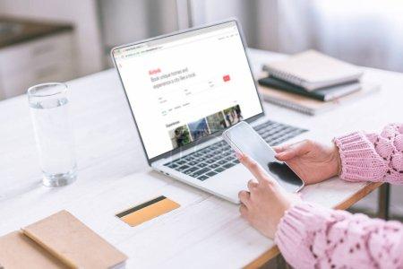 Foto de Recorta la vista de la mujer sosteniendo el teléfono inteligente cerca de ordenador portátil con la Web de Airbnb en pantalla - Imagen libre de derechos