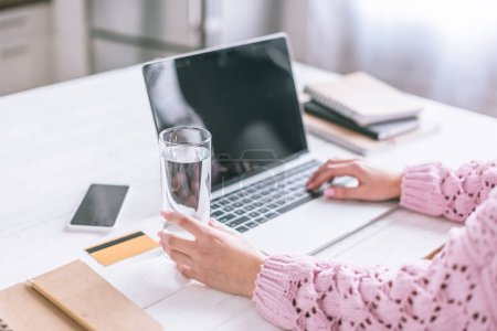 Photo for Cropped view of woman holding glass of water near laptop on wooden desk - Royalty Free Image