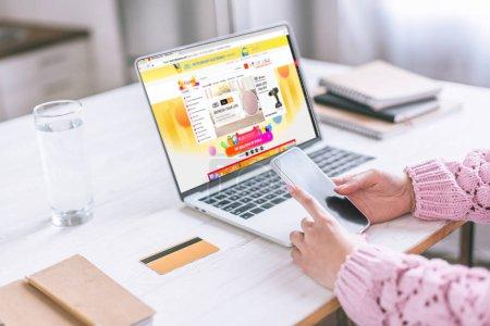 Foto de Recorta la vista de la mujer sosteniendo el teléfono inteligente cerca de portátil con Web site de los Aliexpress en pantalla - Imagen libre de derechos