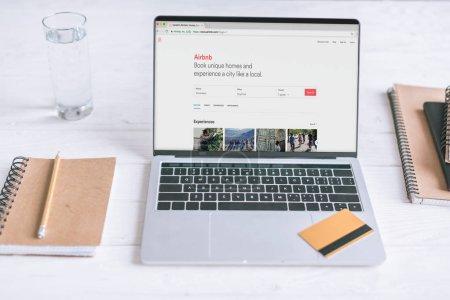 Photo pour Ordinateur portable avec le site Airbnb sur écran et carte de crédit sur le bureau en bois - image libre de droit