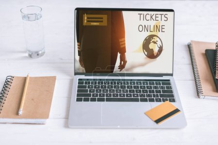 Photo for Laptop with tickets online website on screen and credit card on wooden desk - Royalty Free Image