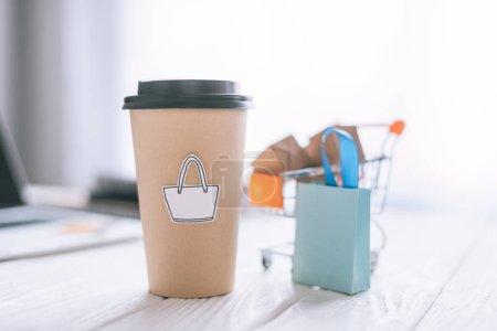 Photo pour Mise au point sélective de gobelet en papier avec symbole près de paquet décoratif et panier avec des boîtes - image libre de droit