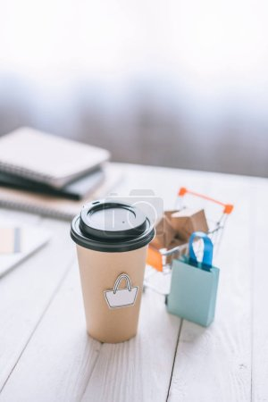 selective focus of paper cup with symbol near toy cart with boxes