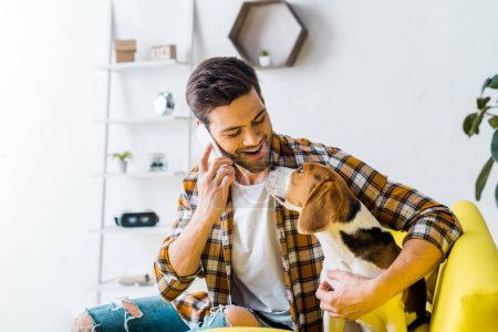 handsome smiling man talking on smartphone and looking at dog