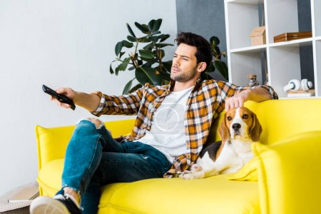 casual man with remote control watching tv and sitting on sofa with dog