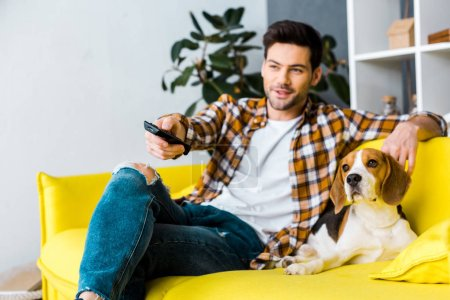 smiling man with remote control watching tv and sitting on sofa with dog