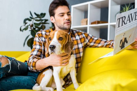 handsome young man reading travel newspaper while sitting on sofa with beagle dog