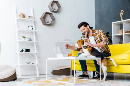 Photo for Smiling male freelancer working on laptop in living room with dog - Royalty Free Image