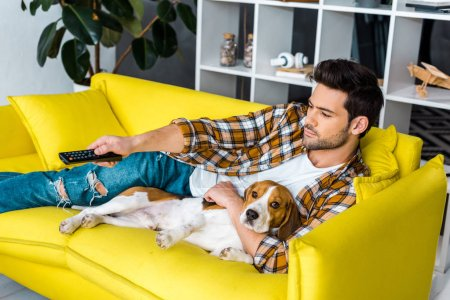handsome man with remote control watching tv and lying on sofa with beagle dog