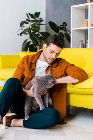 Photo pour Bel homme assis sur le plancher avec chat british shorthair - image libre de droit