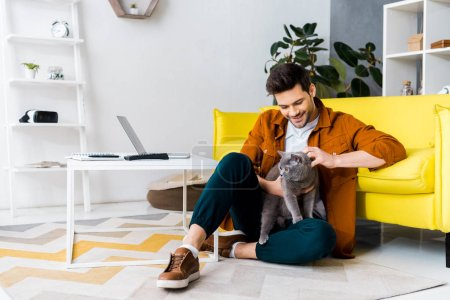 handsome smiling man sitting on floor with british shorthair cat