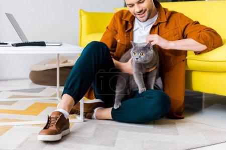 Photo pour Casual homme souriant, assis sur un étage avec chat british shorthair - image libre de droit