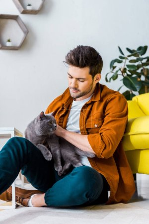 casual smiling man sitting on floor with cute cat