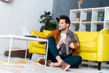 Photo pour Bel homme souriant, à l'aide d'ordinateur portable tout en étant assis sur le plancher avec chat british shorthair - image libre de droit