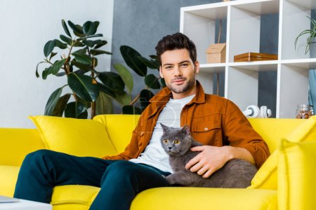 handsome smiling man with british shorthair cat sitting on sofa in living room