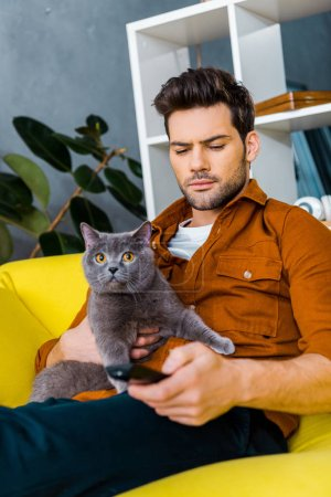 handsome man holding remote control and grey cat at home