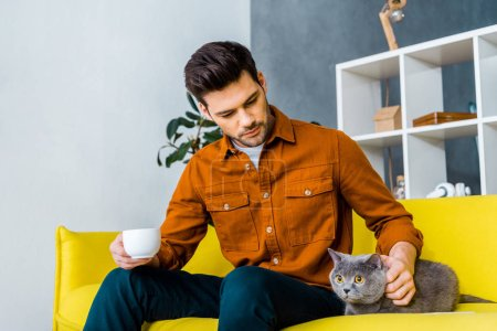 handsome man holding cup of coffee and sitting on sofa with cat