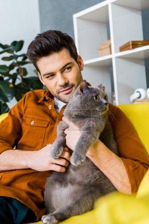 Photo pour Homme heureux avec chat british shorthair, assis sur le canapé à la maison - image libre de droit