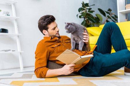 Photo pour Bel homme avec livre et couché sur le sol avec joli chat gris - image libre de droit