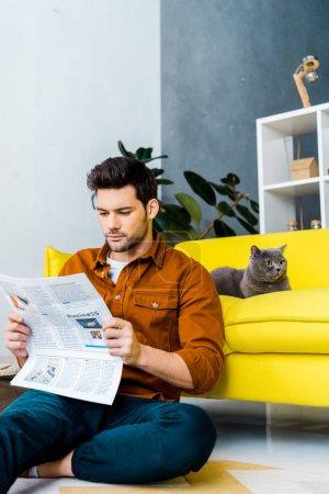 Photo pour Jeune homme lisant journal et assis près de canapé avec chat - image libre de droit