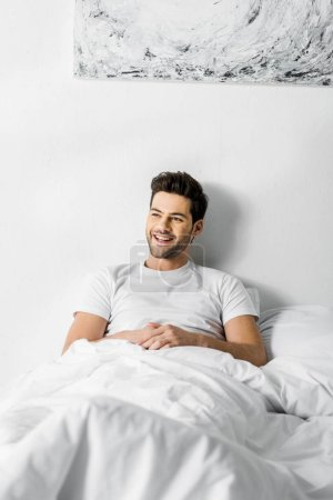 young handsome cheerful man lying in bed in the morning