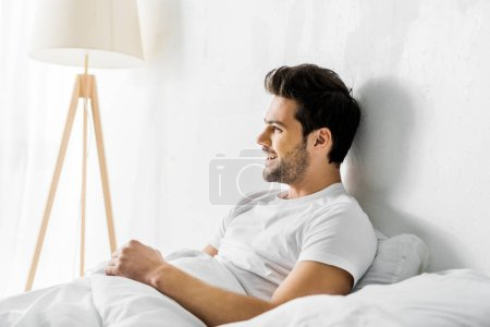 young laughing man lying in bed in the morning