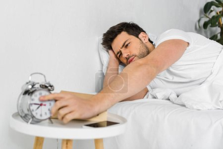 selective focus of man waking up and taking alarm clock in the morning