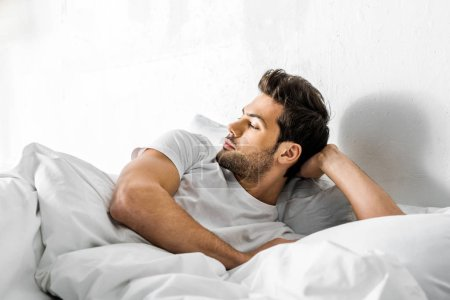 Photo for Handsome man lying in bed and looking away in the morning - Royalty Free Image