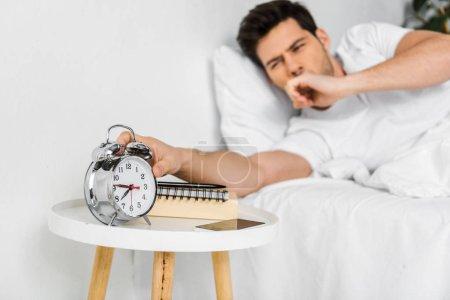 selective focus of yawning man waking up and looking at alarm clock