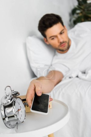 Photo for Selective focus of man waking up and taking smartphone in the morning - Royalty Free Image