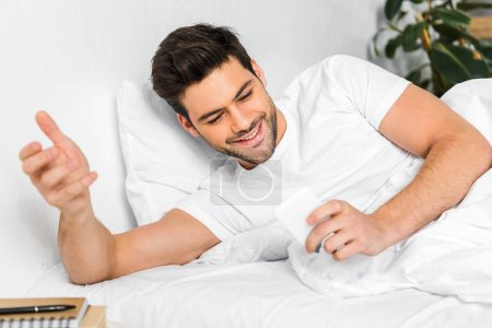 Photo for Cheerful man using smartphone in bed in the morning - Royalty Free Image