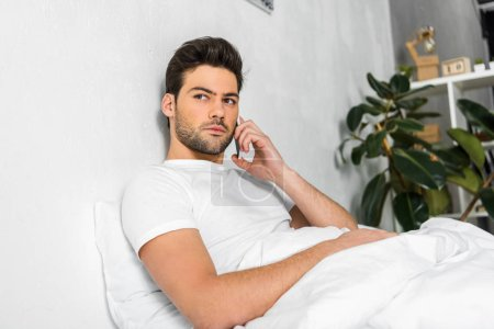 handsome man talking on smartphone while resting in bed in the morning