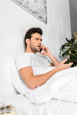 angry man talking on smartphone while resting in bed in the morning
