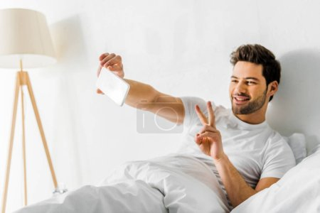 smiling man showing peace symbol while taking selfie on smartphone in bedroom