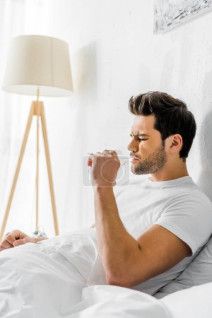 tired man with headache drinking water in bed in the morning