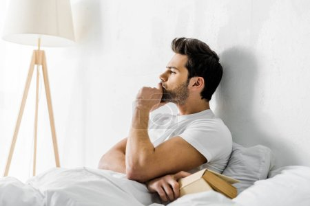 young thoughtful man lying in bed with book