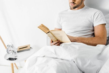 Photo pour Vue recadrée du jeune homme lisant le livre au lit le matin - image libre de droit