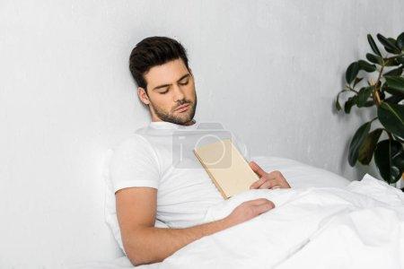 Photo pour Beau jeune homme dormant au lit avec livre - image libre de droit