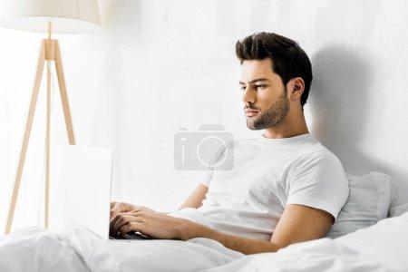 Foto de Hombre serio usando el ordenador portátil en la cama por la mañana - Imagen libre de derechos