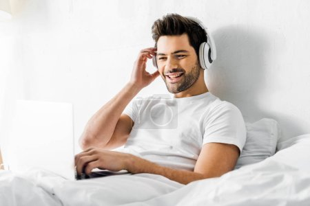 cheerful young man listening music with headphones and laptop in bed