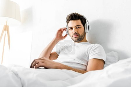 handsome man listening music with headphones and laptop in bed