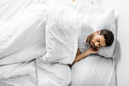 top view of handsome young man sleeping in bed in the morning