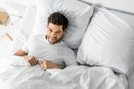 top view of handsome cheerful man lying in bed in the morning
