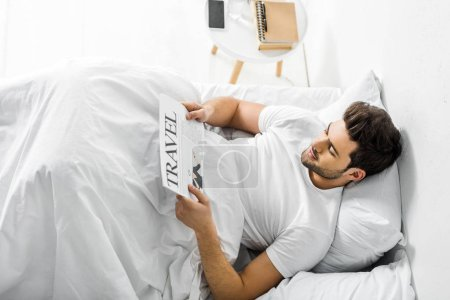 handsome man reading travel newspaper in bed