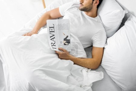 top view of man sleeping in bed with travel newspaper
